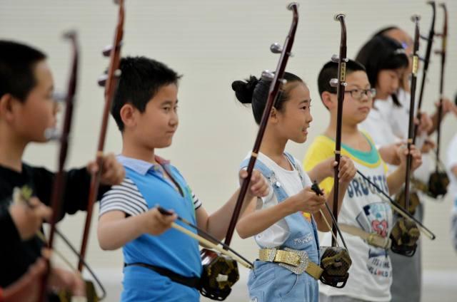 5月29日,在内蒙古妇女儿童中心,孩子们练习二胡合奏曲《喜洋洋》.