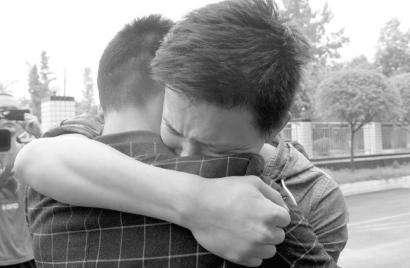 分离了13年的陈良伟兄弟俩拥抱在一起.