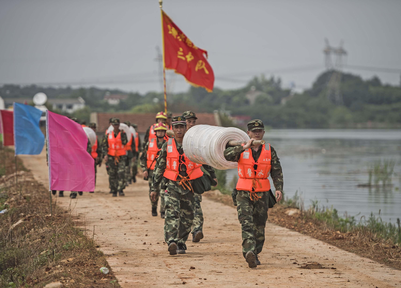 7月13日,武警水电第七支队的战士在牛山湖坝上进行破垸前的准备施工作业。新华社记 者肖艺九摄2