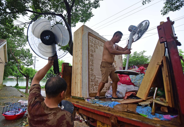 渔场居民在往车上搬家当。新华社记者 程敏 摄
