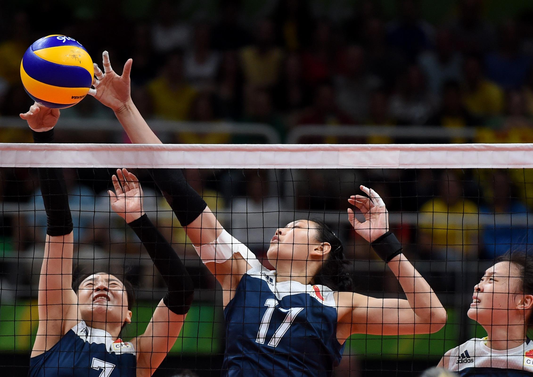 中国队球员魏秋月(左一)、颜妮(中)在比赛中拦网。 当日,在2016年里约奥运会女子排球四分之一决赛中,中国队以3比2战胜巴西队,晋级四强。 新华社记者岳月伟摄