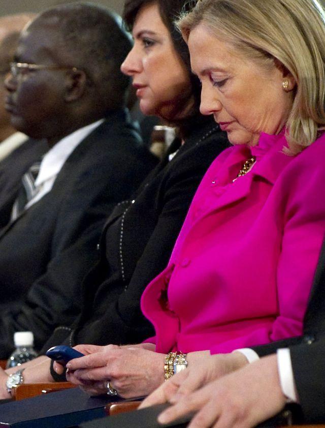 资料:美国国务卿希拉里使用着手机。(图片来源:新华/法新)