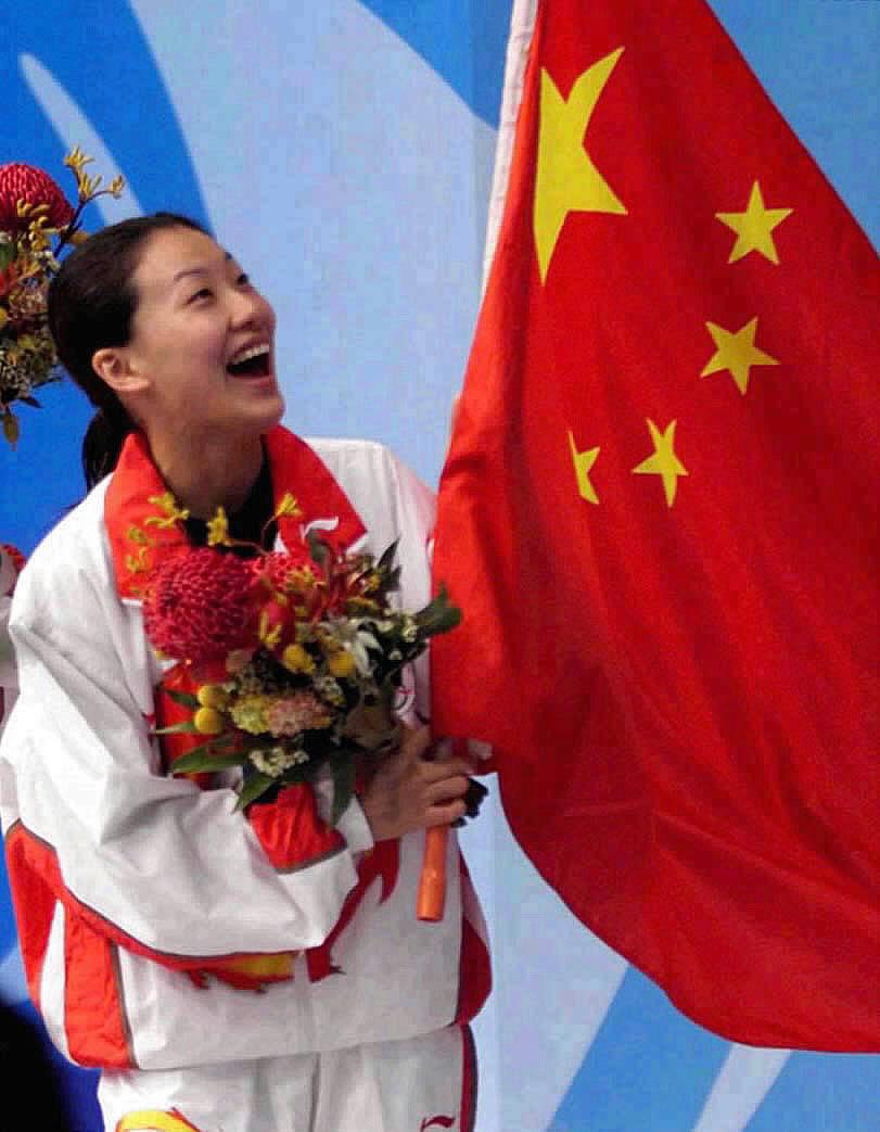 图为2000年9月28日,伏明霞在悉尼奥运会女子3米跳板跳水决赛中夺冠后手执五星红旗向观众致意。新华社发