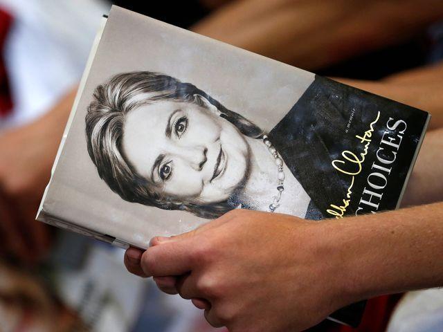 资料:6月22日,希拉里竞选集会,一名支持者手持着希拉里著作《艰难的抉择》。(图片来源:新华/路透)
