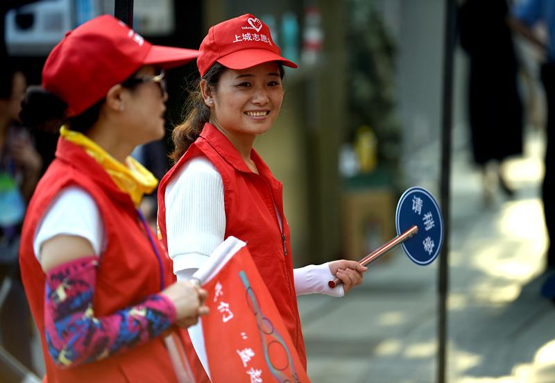 8月24日,来自杭州清波街道的志愿者江丽琴(右)和同伴在杭州柳浪闻莺附近为游客指引道路、维持秩序。 新华社记者 王定昶 摄