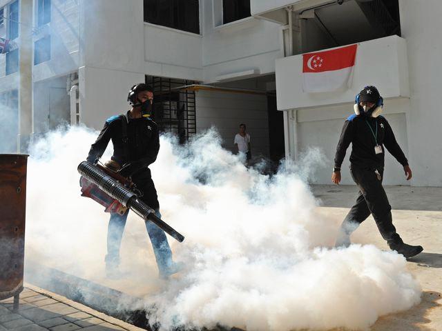 8月31日,新加坡,卫生防疫人员在一处居民区进行防蚊作业。(新华社发)