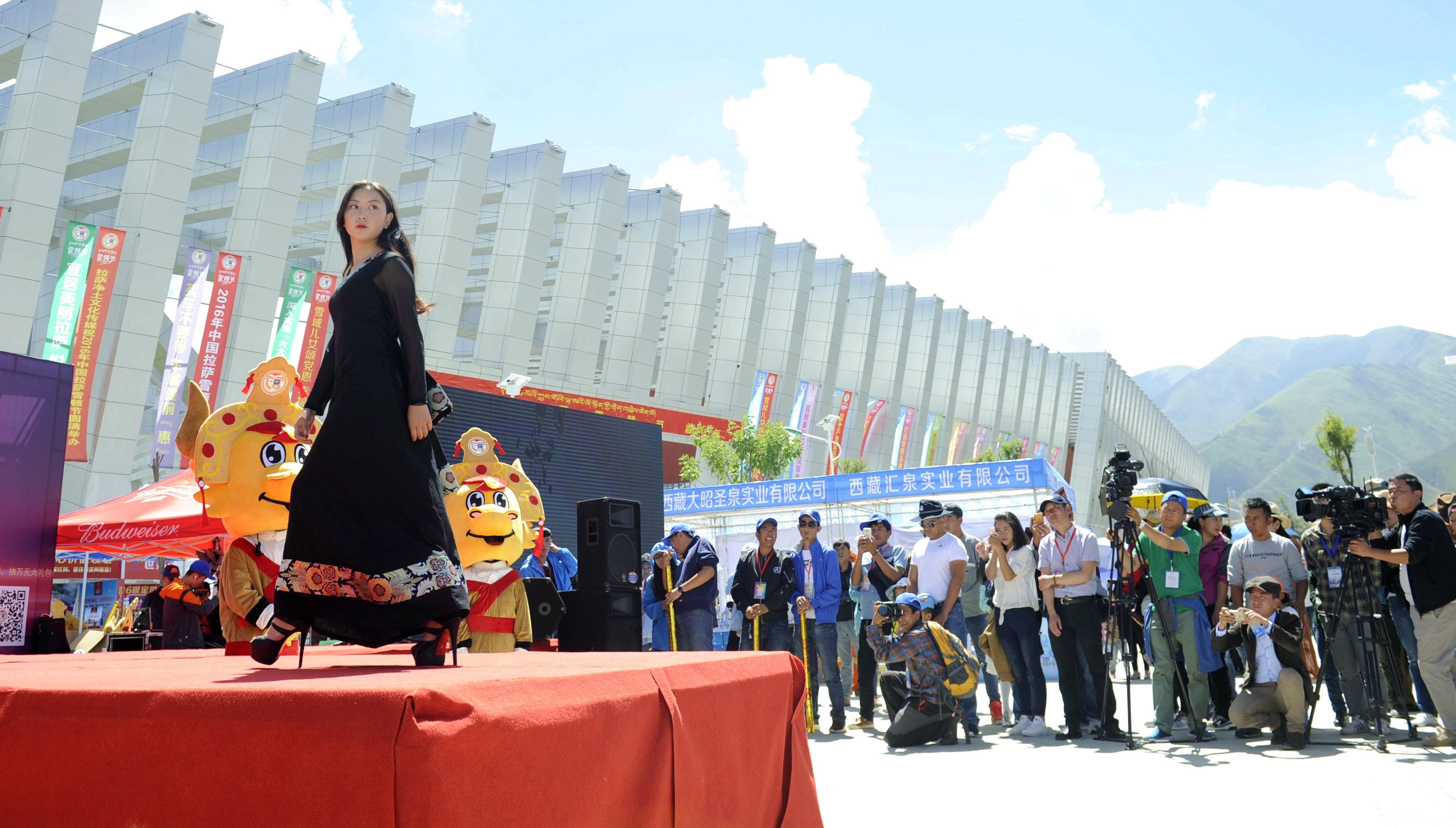 """(模特展示藏族服裝設計師扎西設計的新潮藏裝。 新華社記者晉美多吉攝) 臺下就座的觀眾中,有很多藏族老人。他們時而鼓掌,時而用贊嘆的眼光看著臺上模特身上的服裝。 傳統藏族服飾隨著現代生活方式的普及,也迎來了新生。在繼承古老民族服飾制作的基礎上,很多設計師將簡潔現代的設計元素融入傳統藏裝工藝中,制作出兼具民族、時尚特點的新式藏裝,受到越來越多人的喜愛。 略顯簡易的舞臺,并沒有讓模特們失去了走秀的感覺。穿著黑色藏式鑲邊開襟衫的模特土旦加措顯得格外精神。 """"今天穿的服裝比以前的材質更好,并且更有時尚"""
