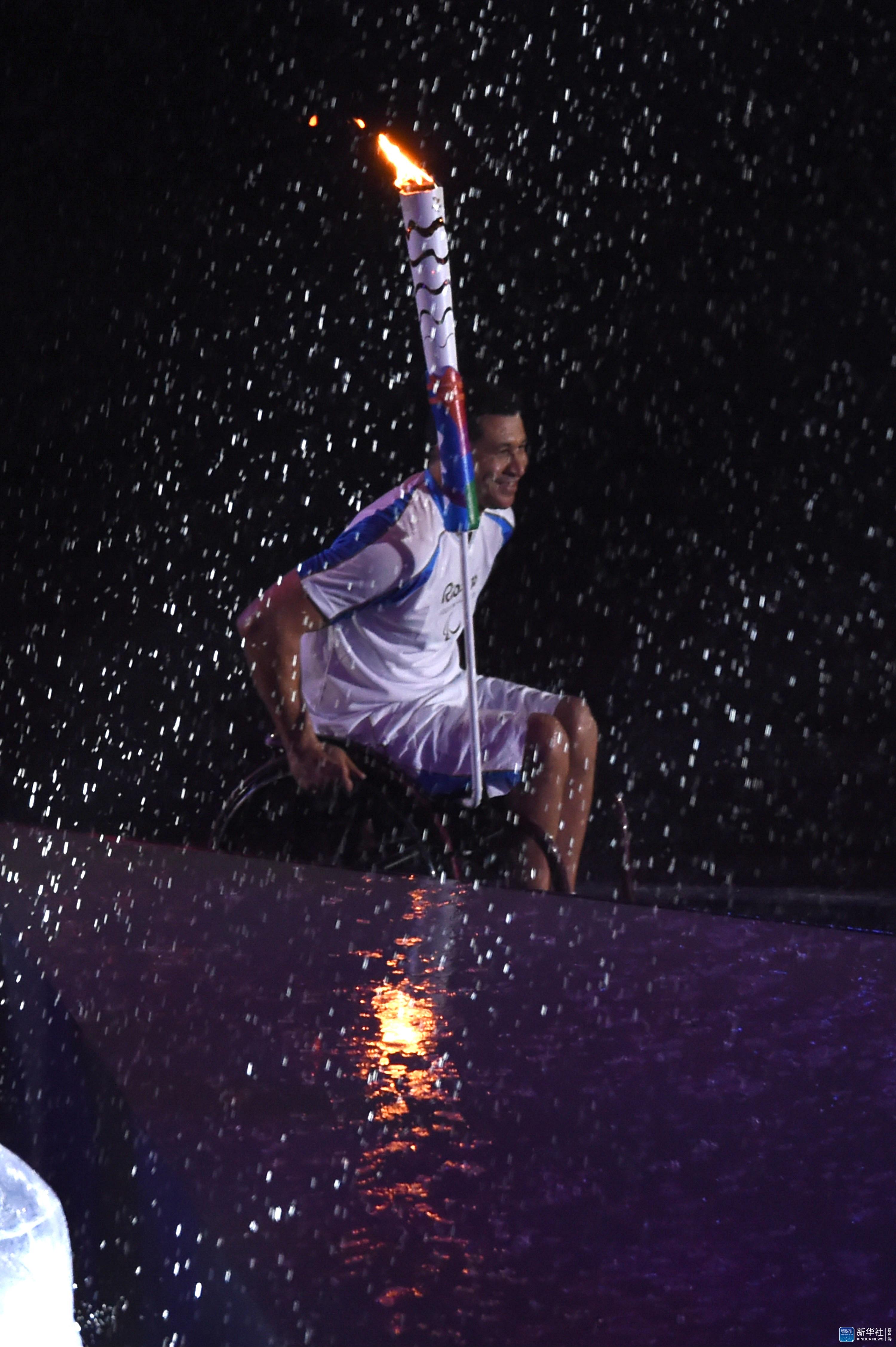 ,巴西残疾人游泳运动员席尔瓦向主火炬进发。当日,第十五届夏季残疾人奥林匹克运动会开幕式在巴西里约热内卢马拉卡纳体育场举行。 新华社记者欧东衢摄