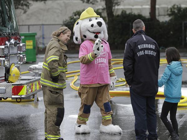 """2015年2月25日, 在加拿大里士满, 身穿粉红色短袖衫的消防局""""吉祥物""""参加反校园暴力活动。(摄影:新华社记者梁森)"""
