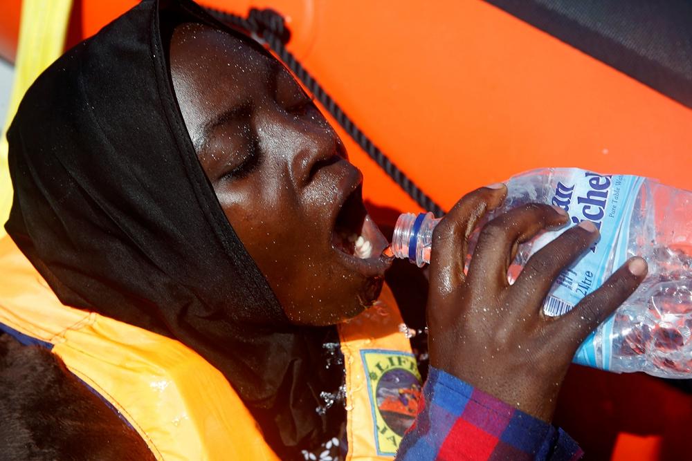(资料照片)8月28日,在地中海海域,一名难民被救援组织营救后喝水。当日,救援人员在地中海海域救起700多名难民。这些难民乘坐橡皮艇从利比亚出发,试图经由地中海前往意大利。(图片来源:新华社/路透)