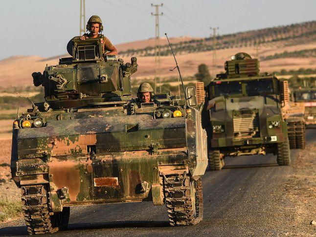 资料:9月2日,一支土耳其装甲部队从叙利亚方向驶回土耳其境内。(图片来源:新华/法新)