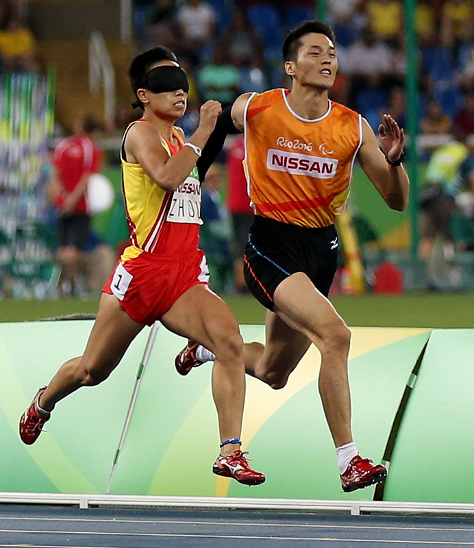9月13日,中国选手周国华(左)、领跑员贾登璞在比赛中。新华社记者 李明 摄