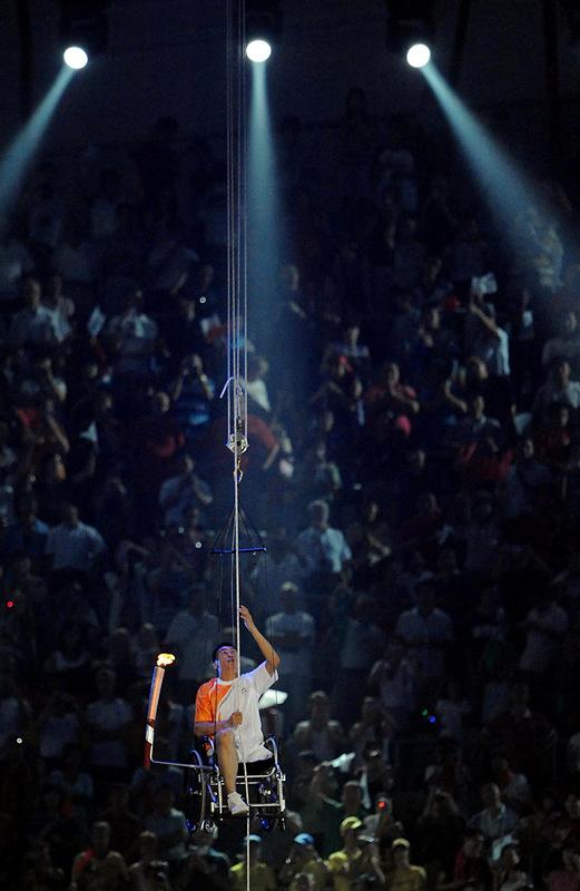 北京残奥会开幕式在国家体育场举行,三届残奥会跳高冠军侯斌将火炬安置在轮椅的支架上,靠双手攀爬将近40米长的绳索,去点燃主火炬。这段艰辛的历程挑战着人类的体能极限,展现出人类坚韧不拔的精神(2008年9月6日摄)。新华社发