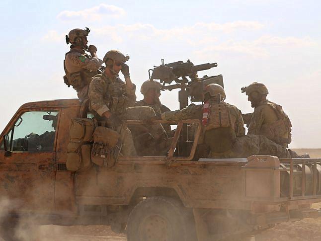 资料:5月25日,据信为美国特种部队的军人乘坐皮卡车行进在叙利亚北部拉卡省一座村庄内。(图片来源:新华/法新)