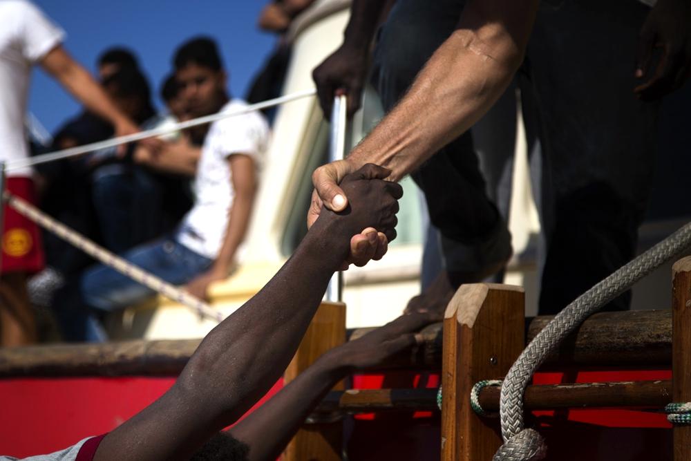 (资料照片)8月20日,在距利比亚海岸约27公里的地中海上,一名尼日利亚移民被拉上救援船只。今年3月底以来,平均每天有20名难民和非法移民试图横跨地中海时溺亡,其中大部分来自撒哈拉沙漠以南的非洲国家,这些人通常从利比亚出发,企图经水路抵达意大利。(图片来源:新华社/美联)