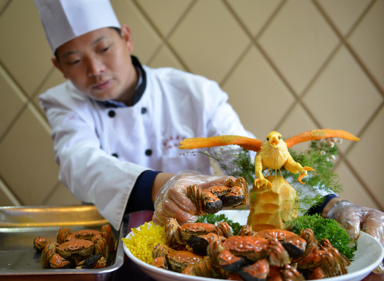 ↑10月18日,江苏省淮安市洪泽区外婆湾大酒店的厨师将大闸蟹装盘。CICPHOTO/王明生 摄