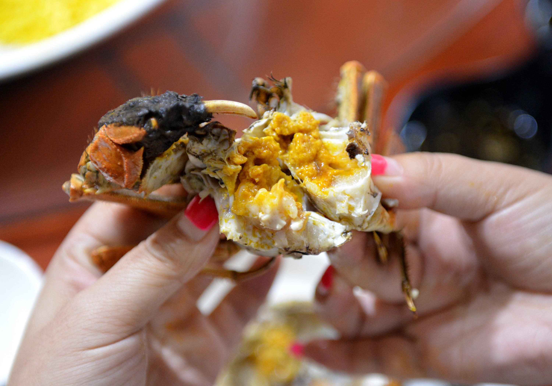 ↑10月18日,游客在江苏省淮安市洪泽区一家餐馆品尝大闸蟹。CICPHOTO/王明生 摄
