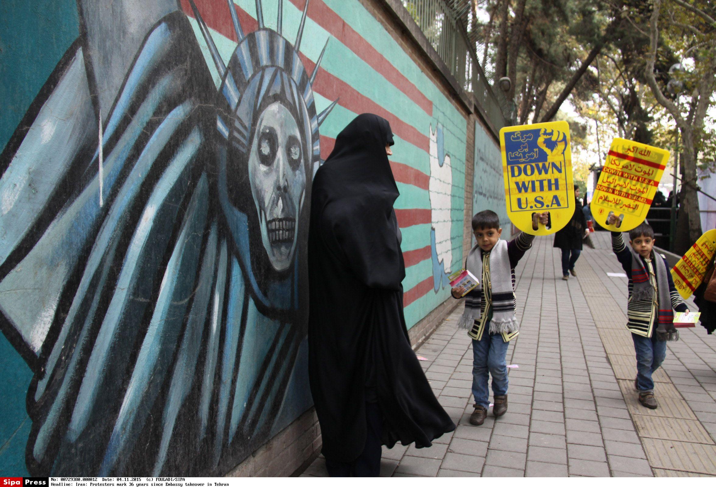 2015年11月4日,伊朗人手持旗帜在美国驻伊朗大使馆旧址外集会,抗议全球自大狂。(新华社/西霸)