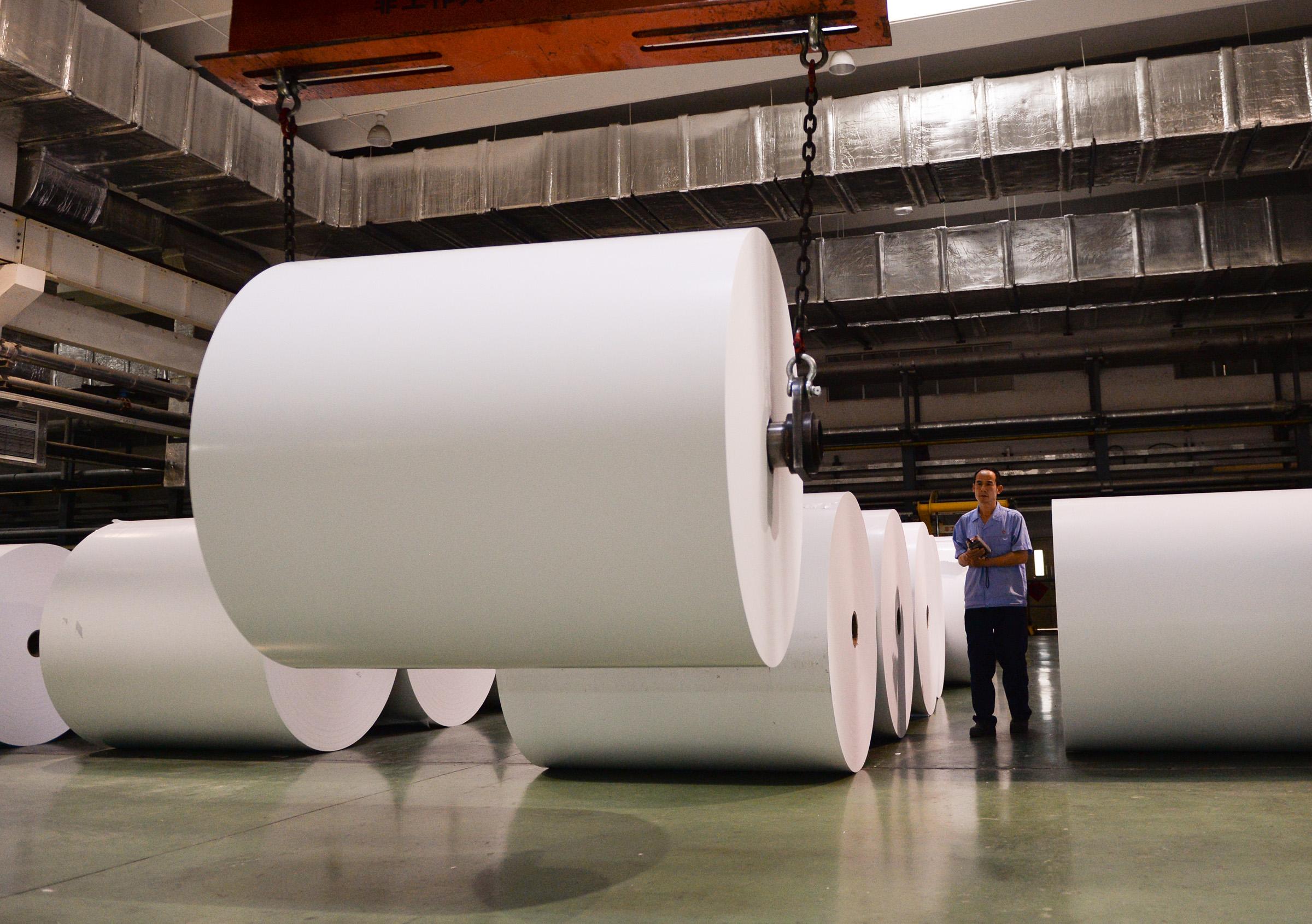 图为工人在调运重达1吨的铜版纸纸卷。(图片来源:新华社)