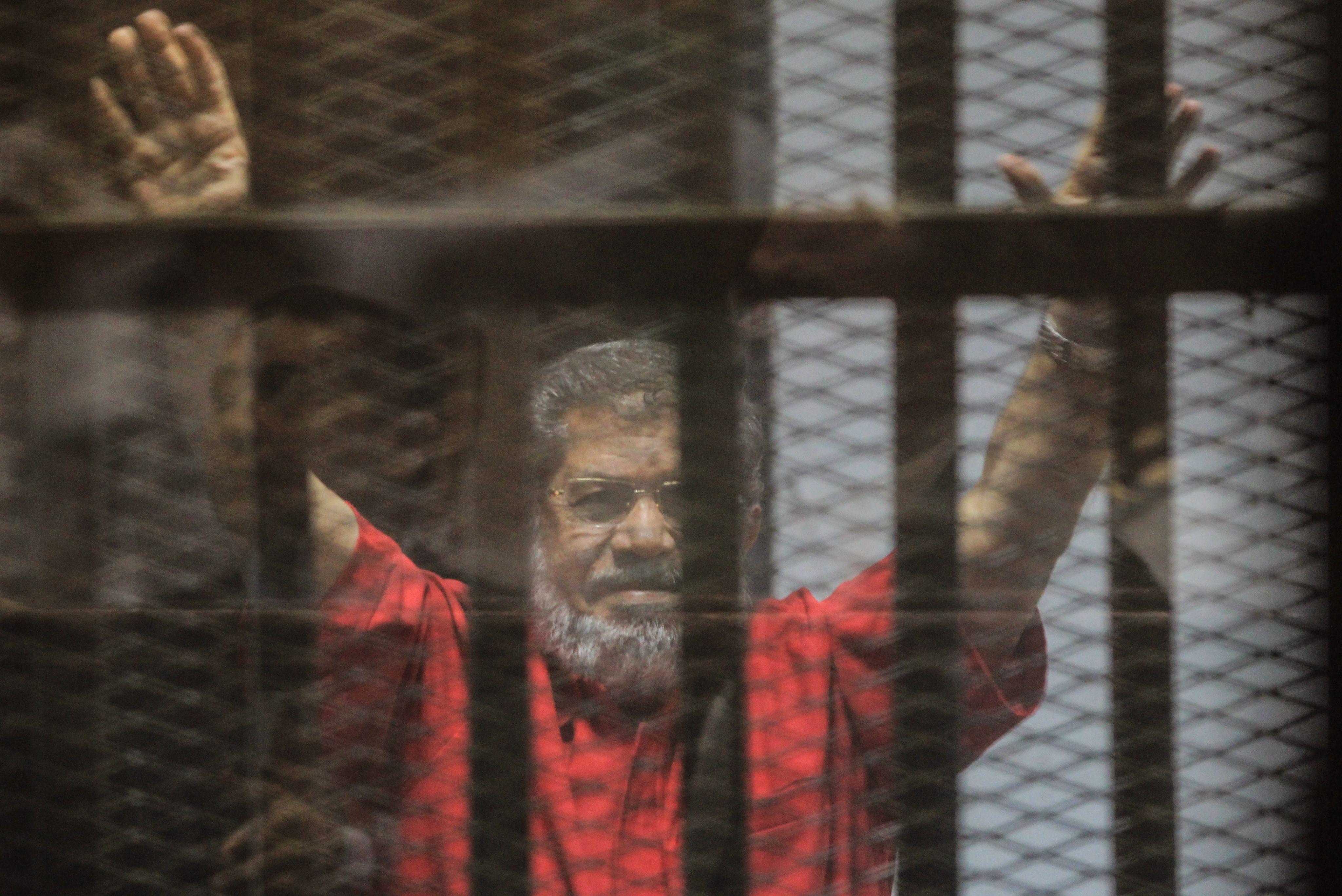 """2016年6月18日,埃及前总统穆尔西在开罗出庭受审。据埃及官方电视台报道,开罗刑事法庭18日宣布,穆尔西因间谍罪以及泄露""""机密文件""""获判40年监禁。(新华社/欧新中文)"""