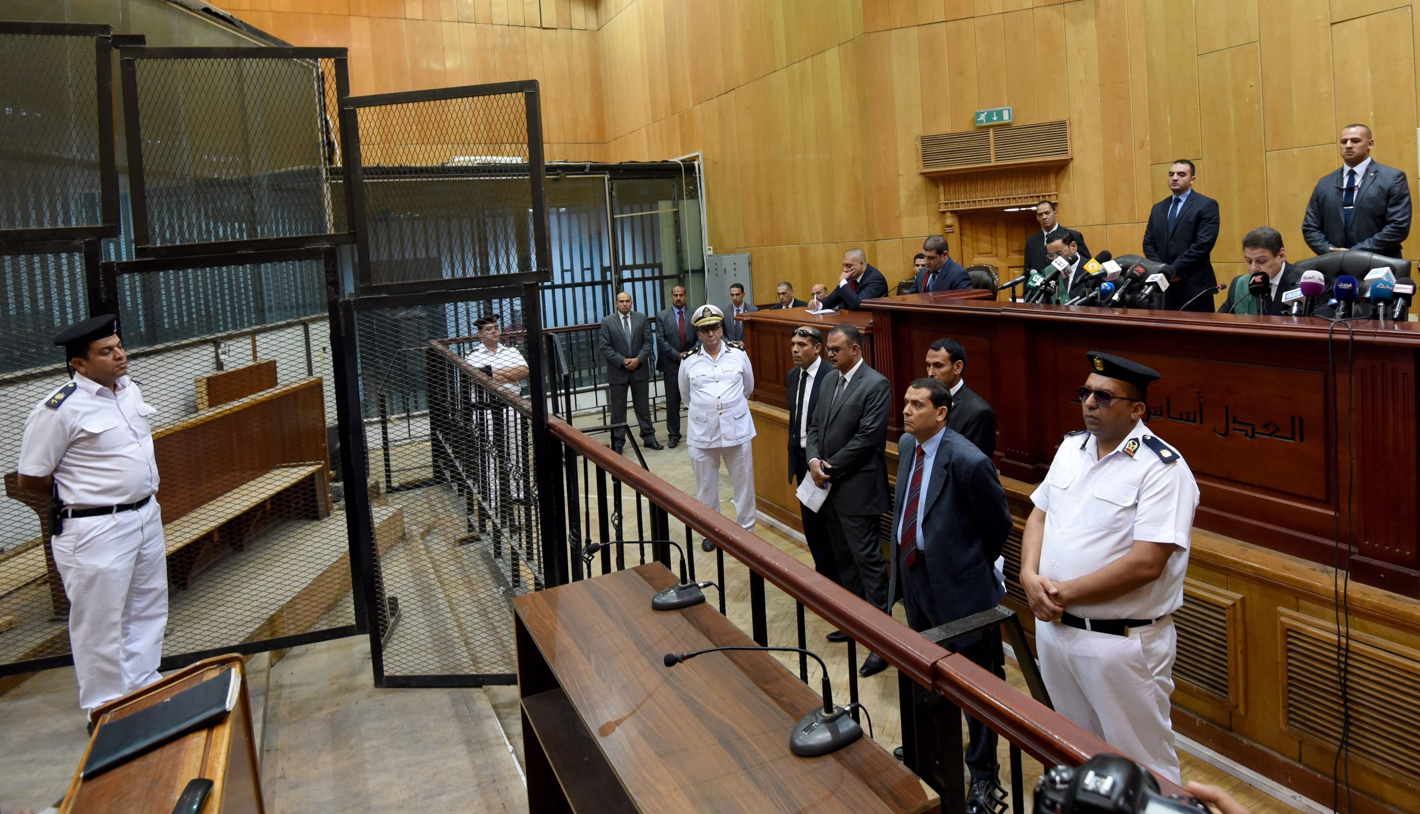 """2016年6月18日,警察、律师和法官在埃及首都开罗出席前总统穆尔西的庭审。据埃及官方电视台报道,开罗刑事法庭18日宣布,穆尔西因间谍罪以及泄露""""机密文件""""获判40年监禁。(新华社/法新)"""