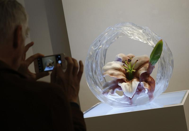 10月27日,在比利时首都布鲁塞尔中国文化中心,一名参观者拍摄琉璃作品《早山一枝春》。(新华社记者叶平凡摄)