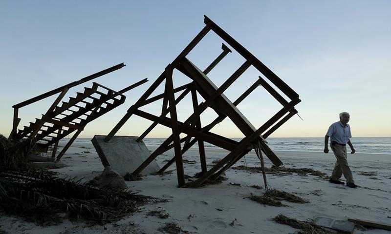 10月8日,在美国佛罗里达州庞特韦德拉比奇,一名男子经过被飓风摧毁的海滨小屋。(图片来源:新华/美联)