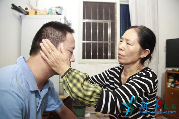 ↑母亲帮周湘虎揉眼睛。李超超摄