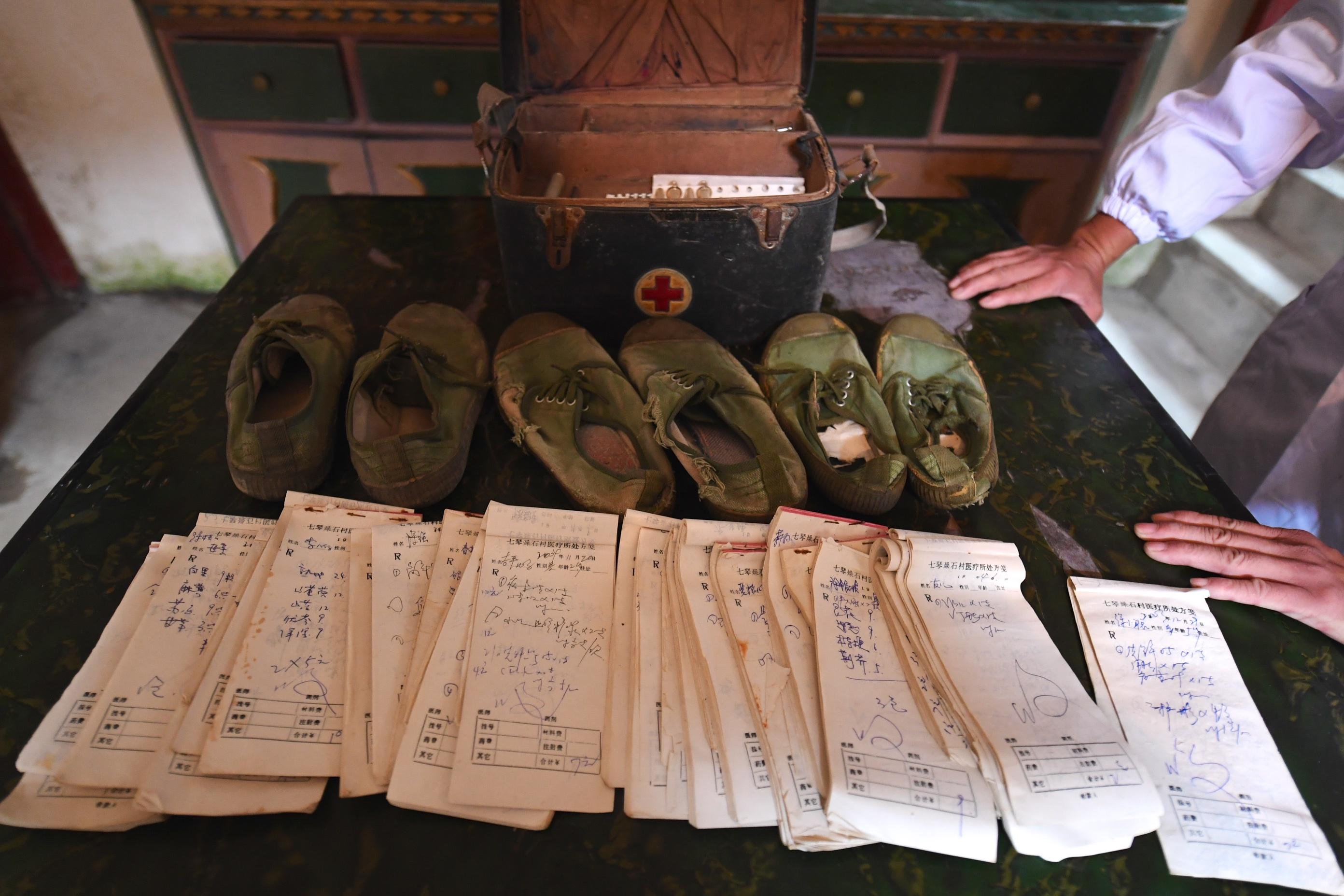 李勤如曾穿坏的解放鞋和出诊的部分单据(11月1日摄)。新华社记者 胡晨欢 摄