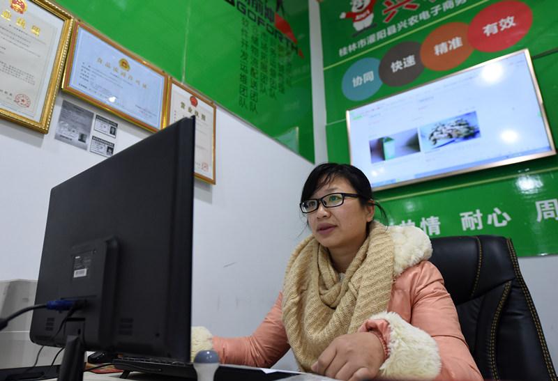 1月26日,在广西灌阳县灌阳镇,一个农村电商网点工作人员在网上联系业务。新华社记者 陆波岸 摄