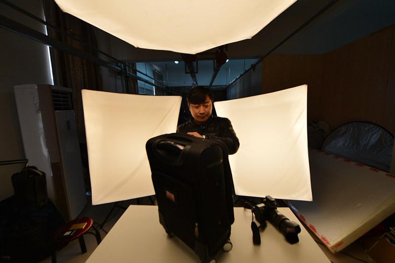10月28日,河北白沟的一名网店摄影师在整理用于拍照的箱包。新华社记者 牟宇 摄