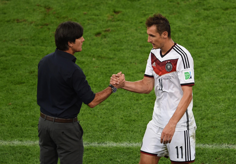 ↑德国队球员克洛泽(右)被替换下场后与主教练勒夫握手致意