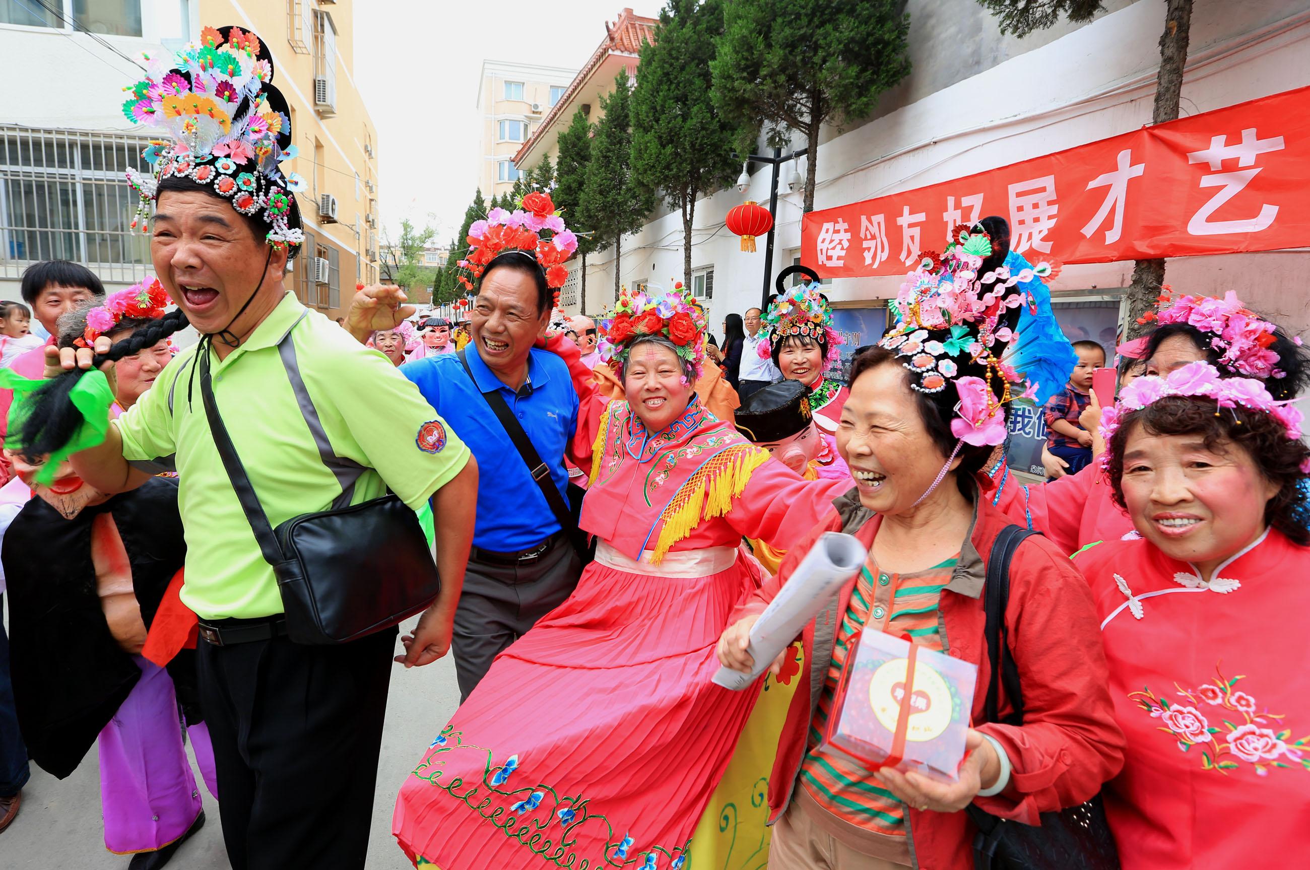 """2016年5月25日,在北京市怀柔区泉河街道""""邻里节""""上,来自高雄大寮区中兴里的23名台湾同胞与社区居民一起参加""""小车会""""表演。"""