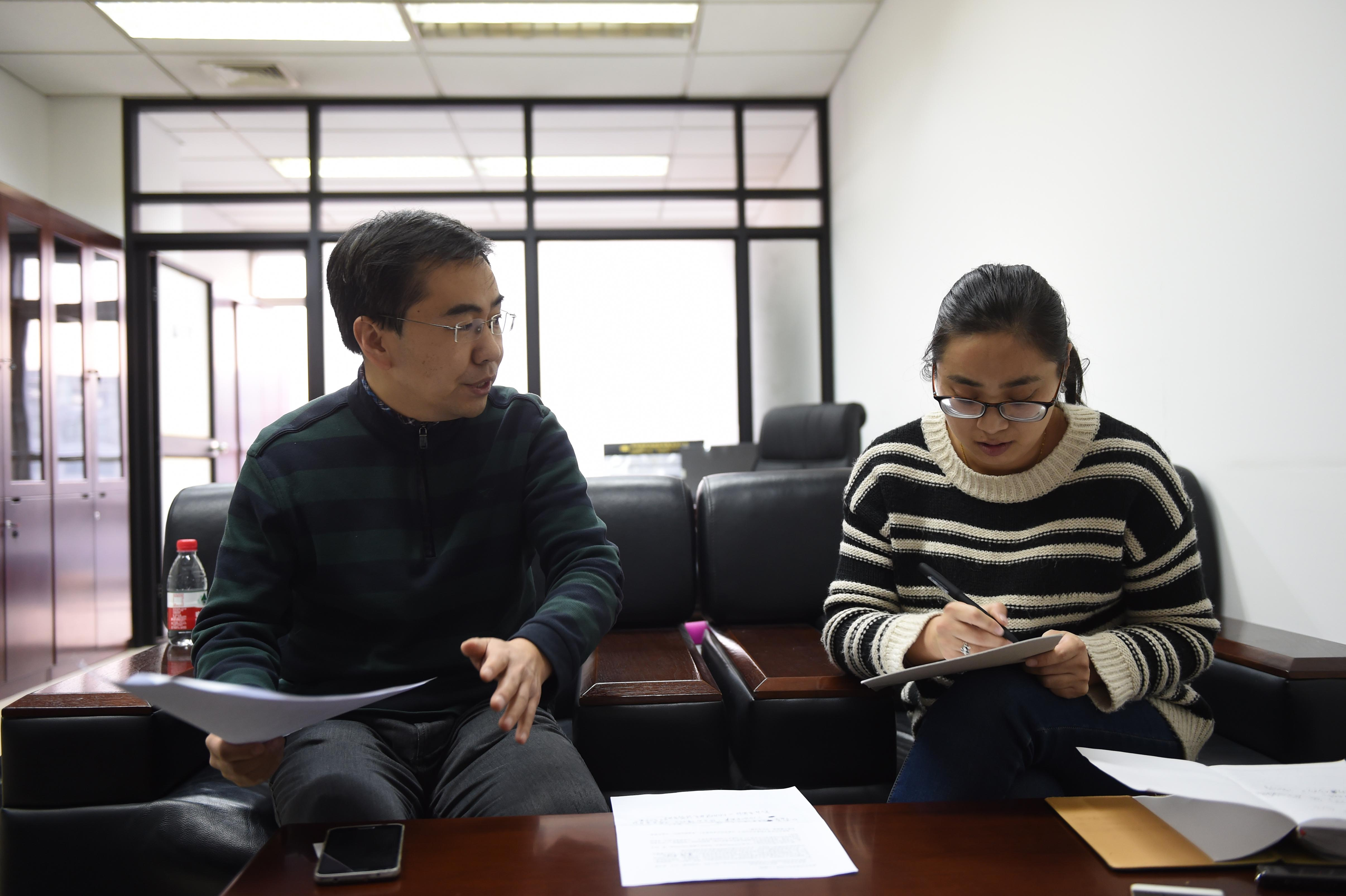 12月13日,中关村二小校长杨刚(左)接收新华社记者采访。 (新华社记者李文摄)