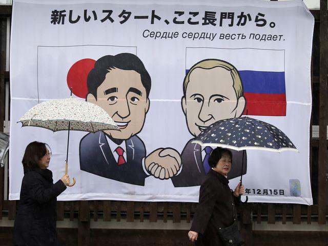 12月14日,两名行人从日本首相安倍晋三与俄罗斯总统普京会晤宣传画旁走过。(新华/美联)