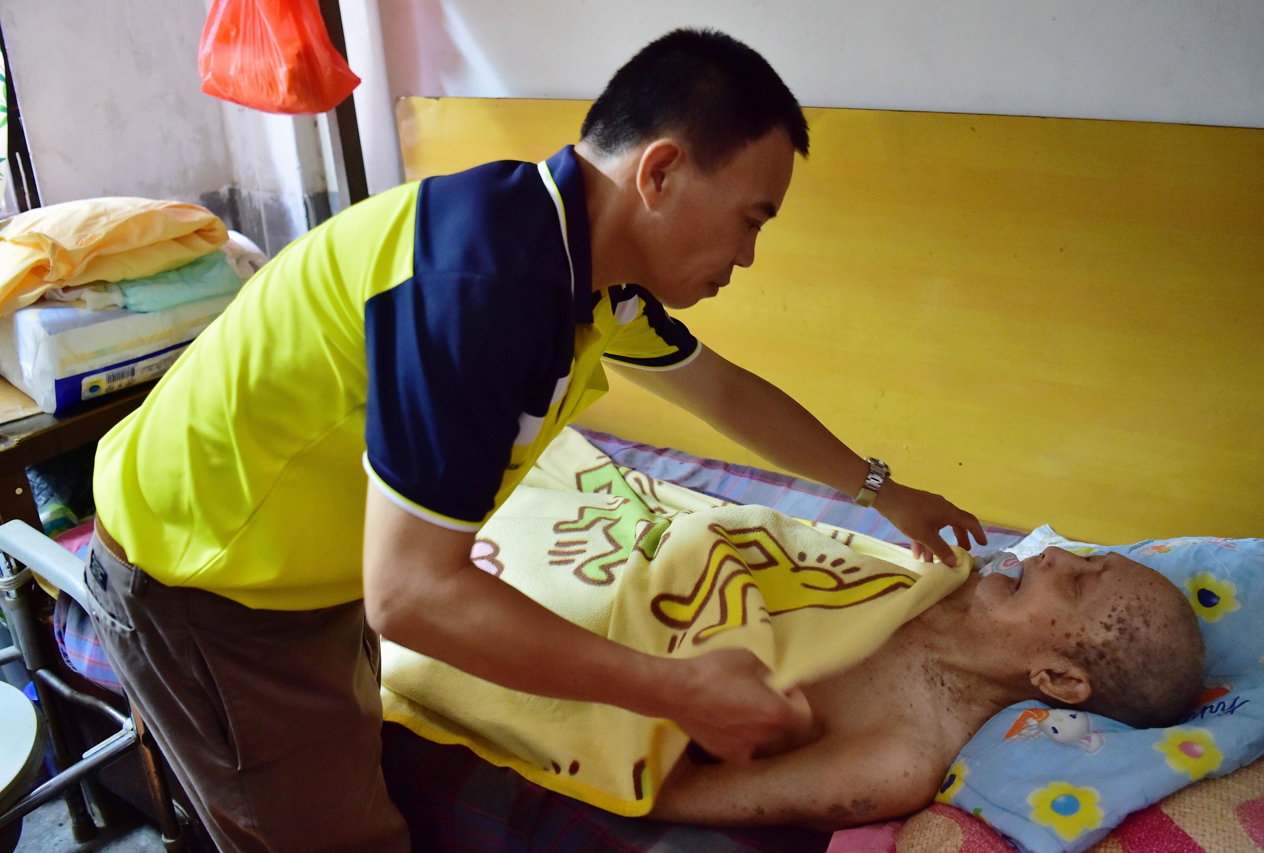 2016年6月19日,高雄市左营区祥和里里长刘德文(左)正在照顾96岁的抗日老兵蔡万章。(新华社记者 魏培全摄)