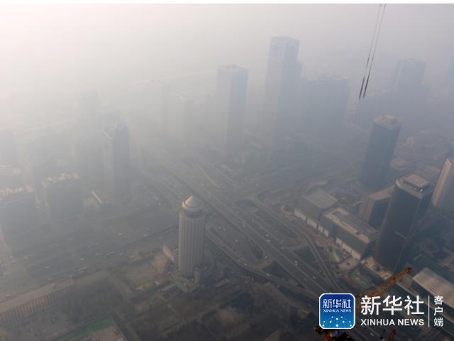 17日从北京在建第一高楼中国尊楼顶,拍摄的雾霾笼罩下的CBD。
