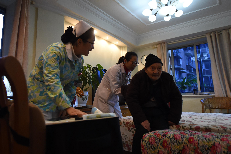 12月20日,家庭医生工作室的刘露霞医生(左二)带领医护团队在社区居民家中为老人检查身体。新华社记者 唐奕 摄
