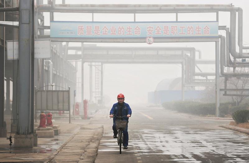 12月20日,在因雾霾停产的菏泽金盛热力有限公司内,一名留守工作人员骑车经过厂区。新华社记者 才扬 摄