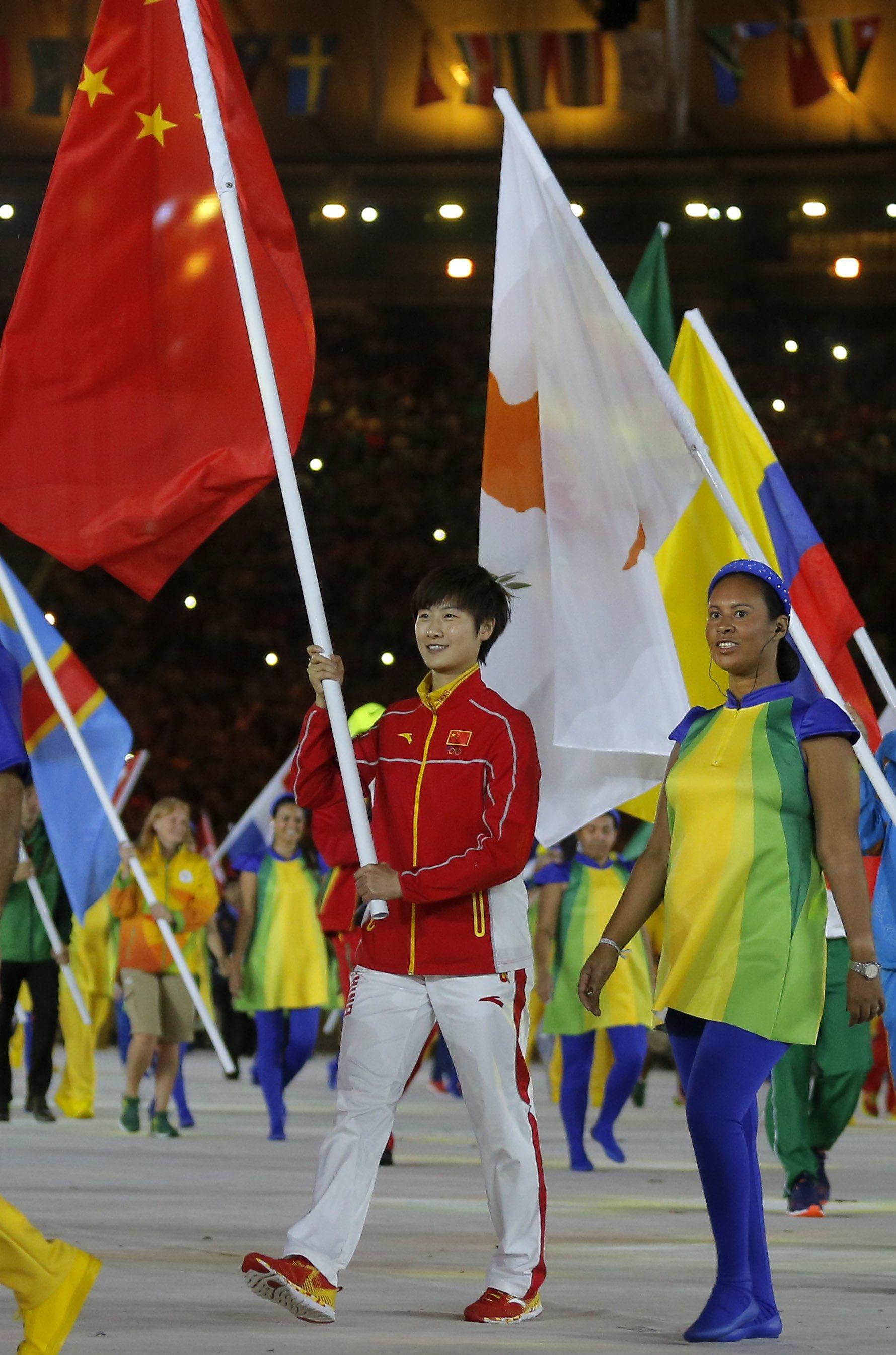 ↑中国代表团旗手丁宁(左)进入体育场