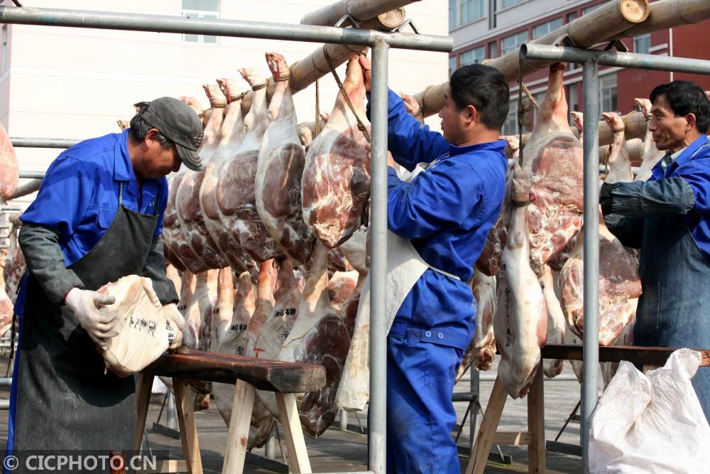 """↑12月2日,员工在晒出""""立冬""""时腌制的火腿。CICPHOTO/包康轩 摄"""