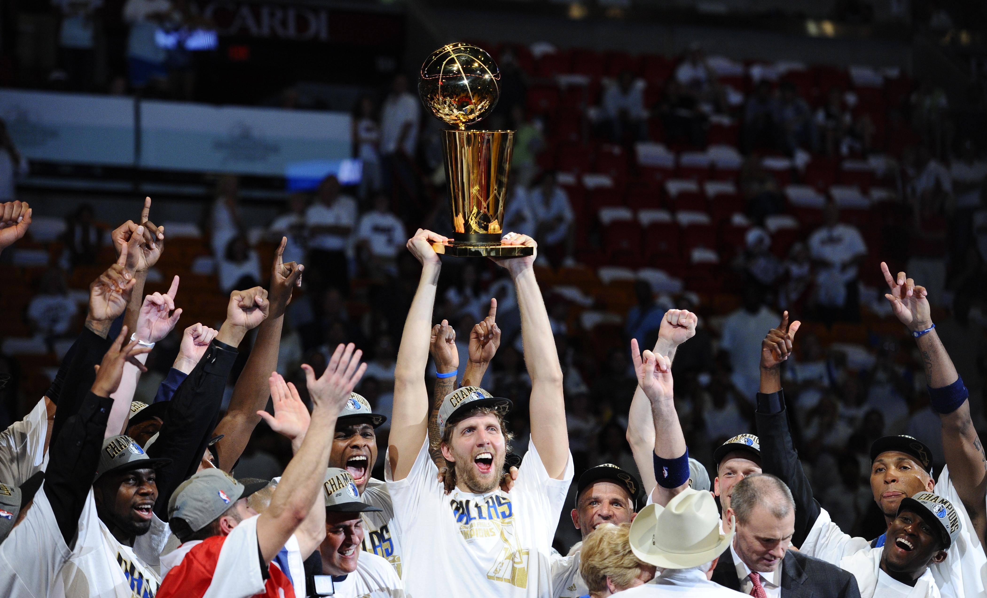 在美国迈阿密进行的NBA总决赛第六场比赛中,客场作战的达拉斯小牛队以105:95击败迈阿密热火队,从而以总比分4:2首次夺得NBA总冠军。图为小牛队德国前锋德·诺维茨基(中)高举冠军奖杯与队友一同庆祝胜利。 新华社外代图片 北京 2011年06月14日 新华社/EPA欧新