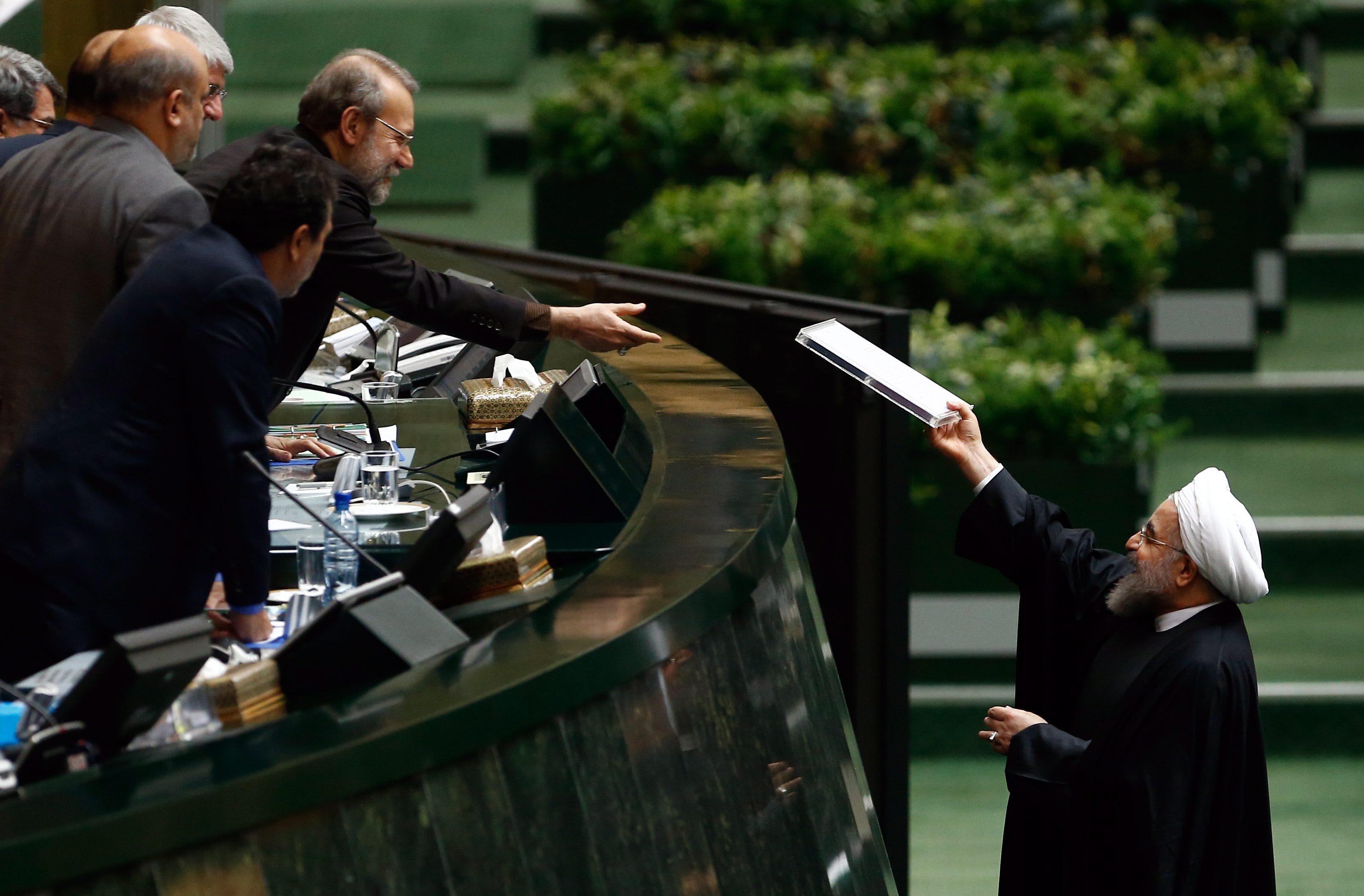 1月17日,在伊朗首都德黑兰,伊朗总统鲁哈尼(右)向议会递交年度预算。鲁哈尼17日表示,伊核问题全面协议正式执行后,伊朗与世界的关系已经开启了新篇章。经过马拉松式艰难谈判,伊朗与伊核问题六国(美国、英国、法国、俄罗斯、中国和德国)于2015年7月14日达成伊核问题全面协议。根据协议,伊朗将限制其核计划,作为交换,国际社会将解除对伊朗制裁。(新华社外代图片 北京2016年1月18日 新华社/欧新中文)