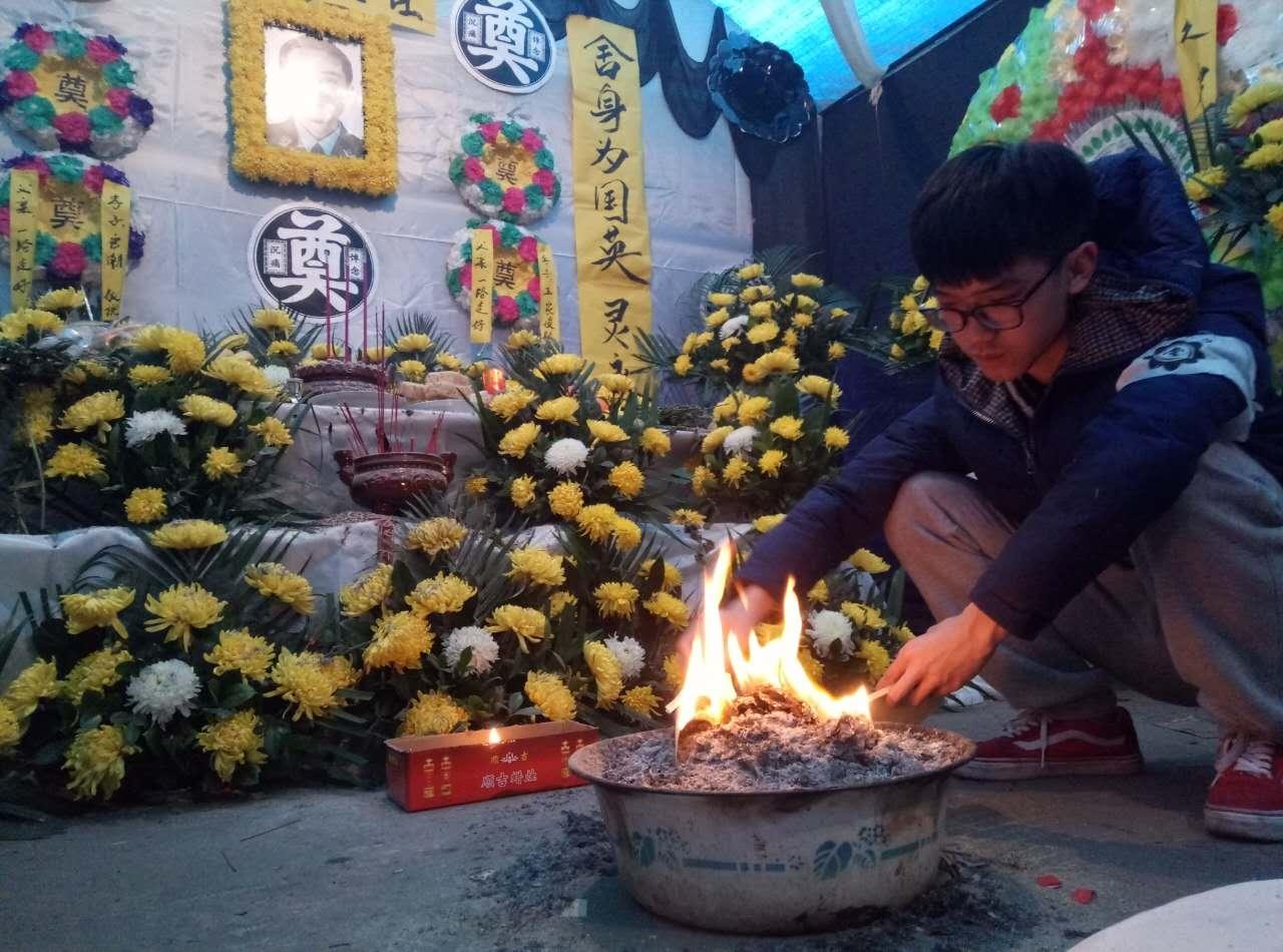 12月16日,唐鸿的儿子唐潮在父亲灵位前。 (新华社记者 李力可 摄)