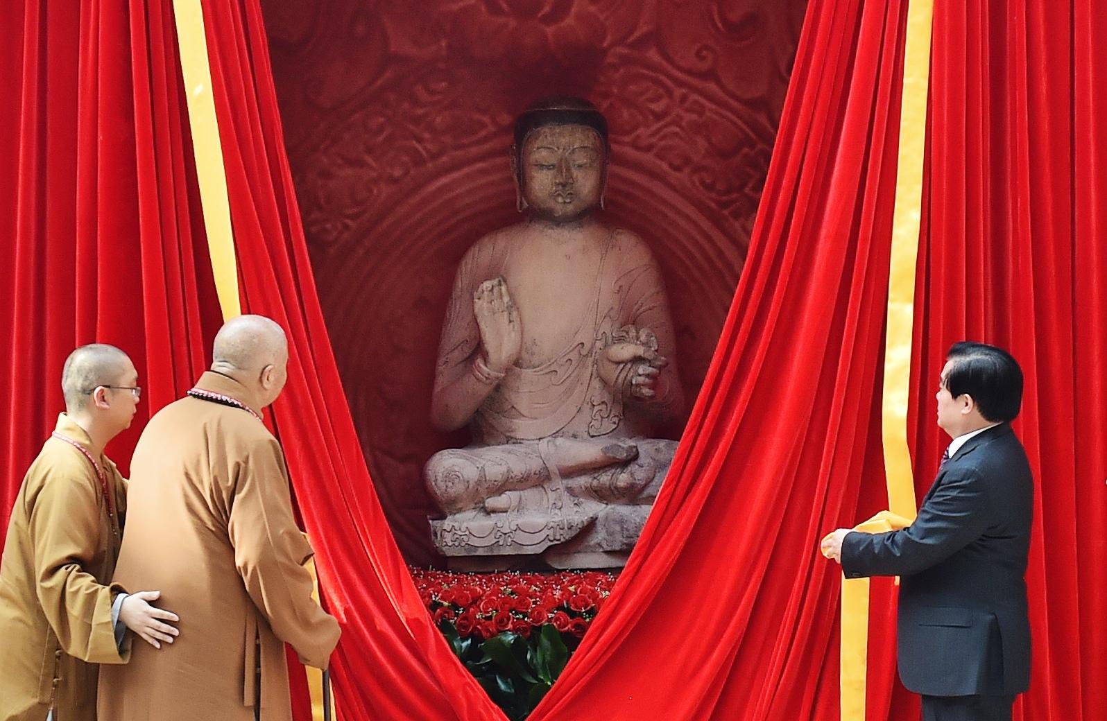 2016年4月30日,流失境外近20载的北齐佛首与佛身合璧入藏河北博物院,星云大师(左二)等为佛像揭幕。(新华社记者 王晓摄)