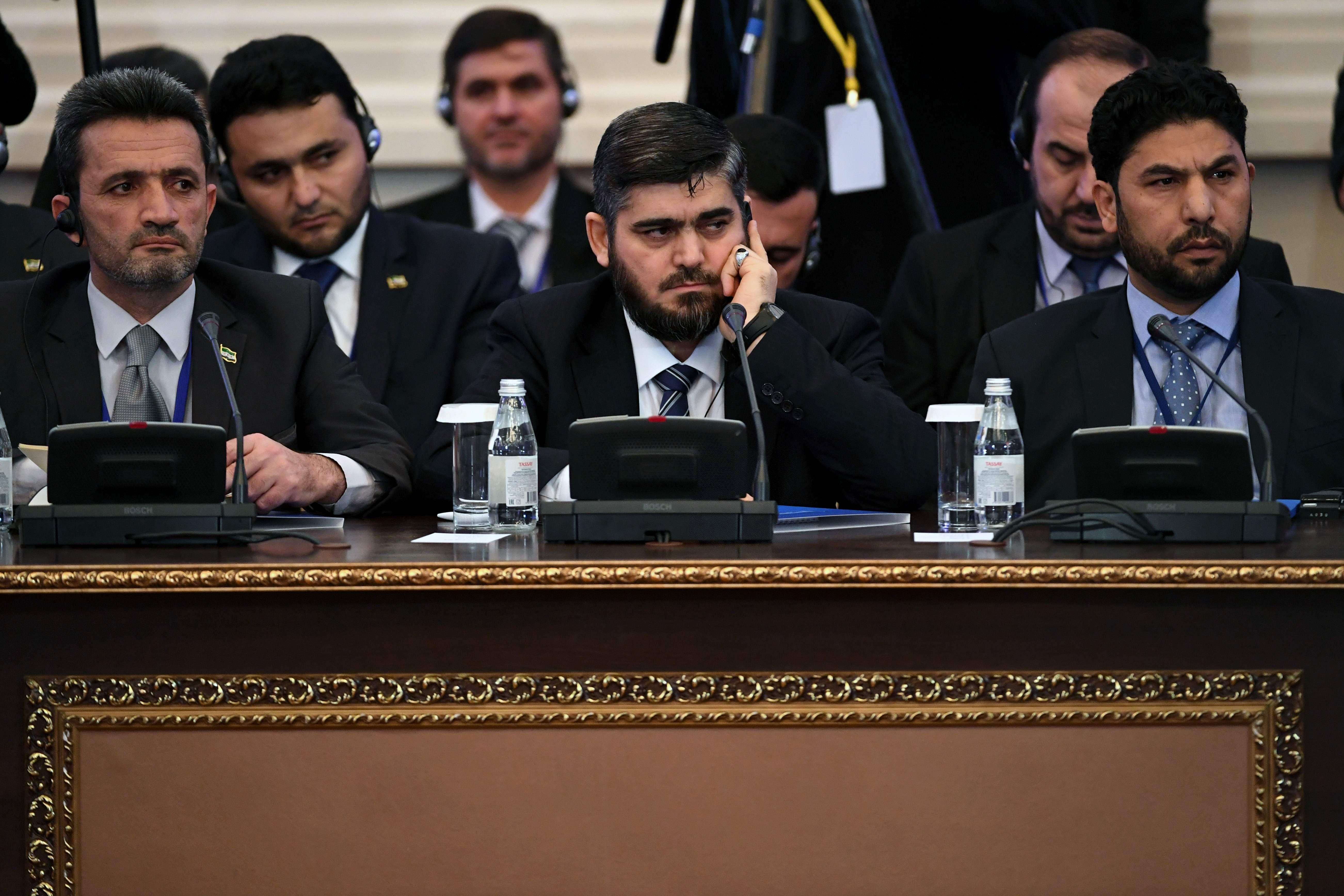 1月23日,叙利亚反对派代表团团长阿鲁什(中)出席在阿斯塔纳举行的叙反对派武装与政府的和谈。(新华社/法新)