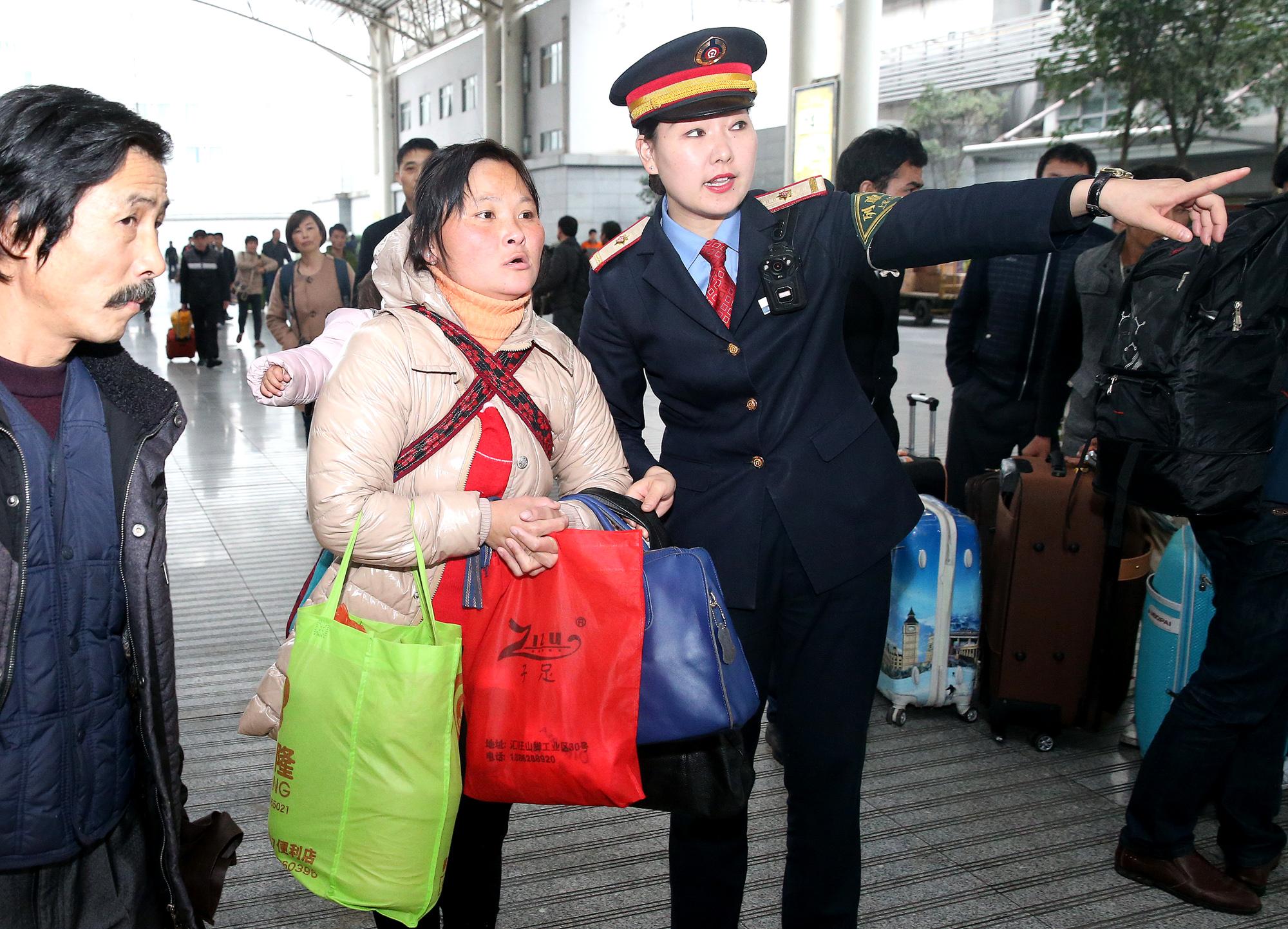 1月18日,沪港列车车长李喆(前右)正在上海火车站协助旅客出站。