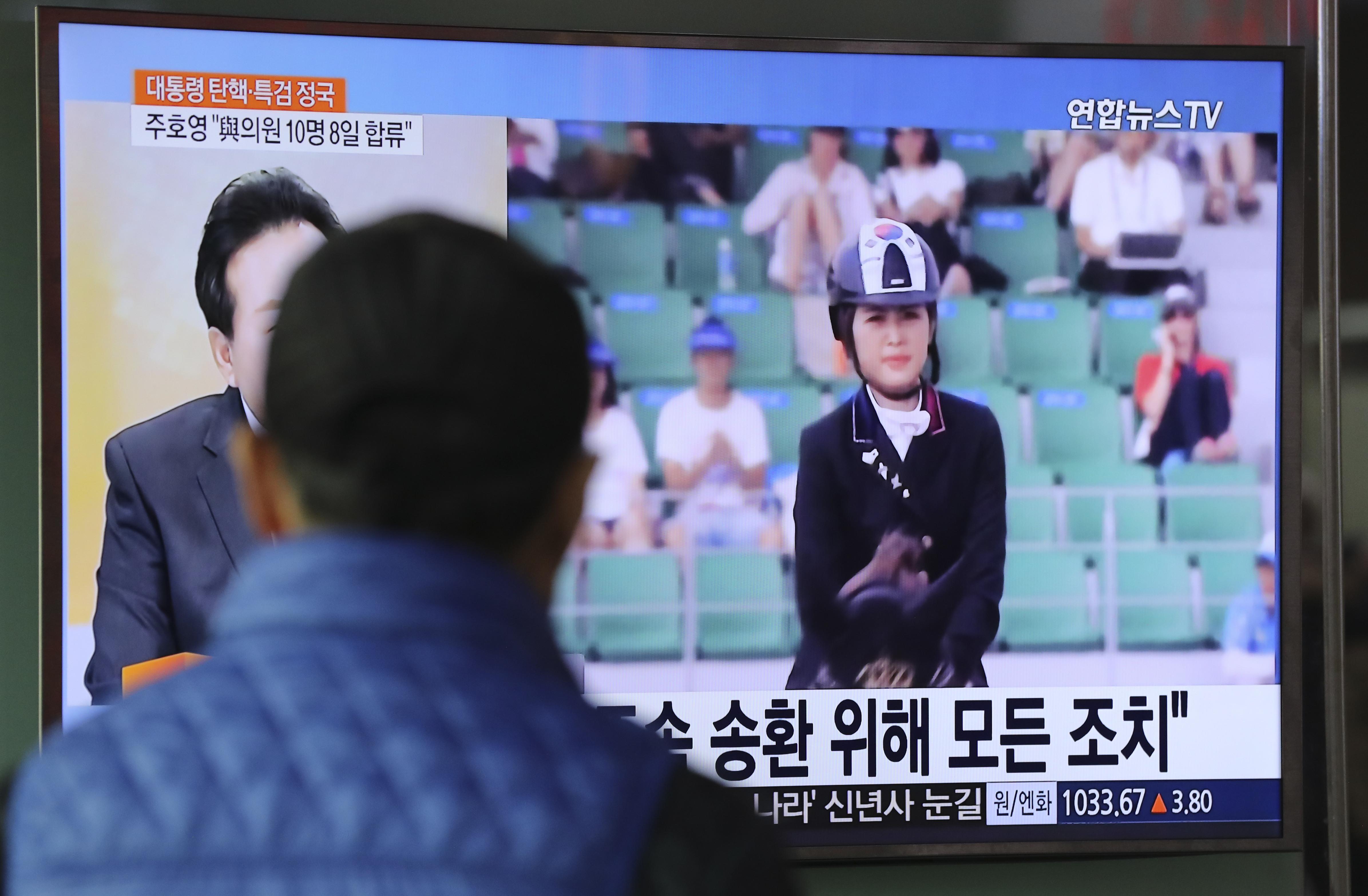 1月2日,在韩国首尔,一名男子观看崔顺实之女郑某被拘的新闻。(新华社/美联)