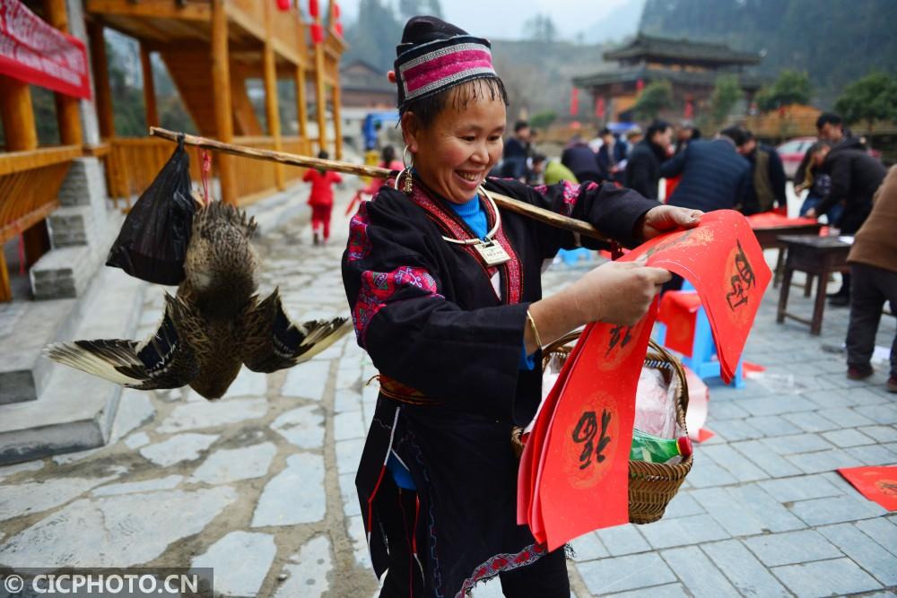 ↑1月16日,贵州省剑河县观么镇巫包苗寨村民在欣赏刚领到的春联。CICPHOTO/杨文斌 摄
