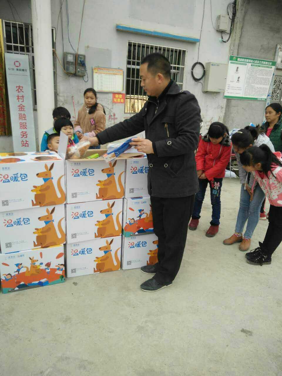 杨华根到学校给孩子们发放礼包。